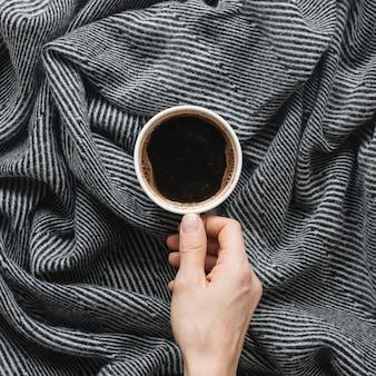 Tazza di caffè della holding della mano della persona sopra il panno