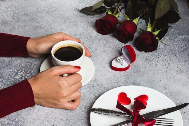 Tazza di caffè della mano della donna della regolazione della tavola romantica di giorno di biglietti di s. valentino della tenuta