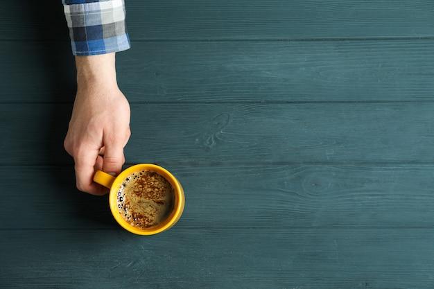 Tazza di caffè della stretta della mano dell'uomo con schiuma schiumosa su di legno