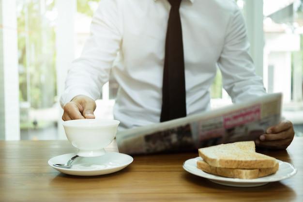 Tazza di caffè della tenuta della mano dell'uomo d'affari e giornale di lettura con la fetta di pane tostato