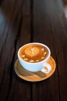 Tazza di caffè di arte del latte sulla tavola di legno
