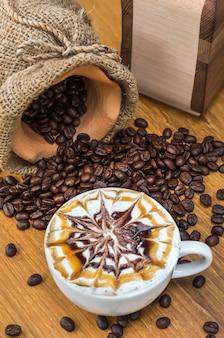 Tazza di caffè di arte di larte sulla tavola di legno con i chicchi e la smerigliatrice di caffè tradizionali
