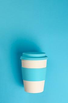 Tazza di caffè di bambù riutilizzabile con supporto in silicone e coperchio su sfondo blu.