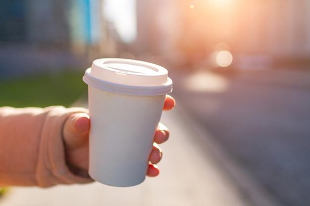 Tazza di caffè di carta della tenuta della giovane donna un giorno soleggiato