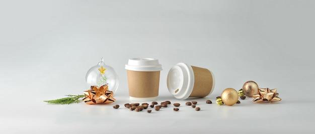 Tazza di caffè di carta e chicchi di caffè su priorità bassa bianca.