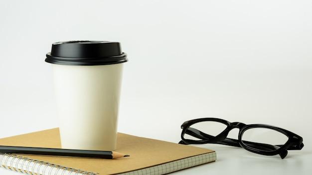 Tazza di caffè di carta e un taccuino sul fondo bianco dello scrittorio con lo spazio della copia. - forniture per ufficio o concetto di educazione.