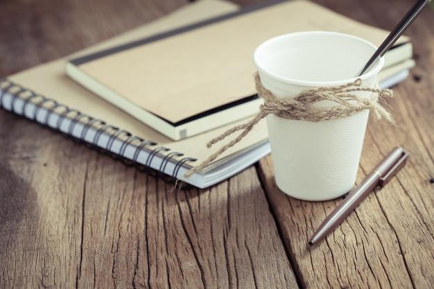 Tazza di caffè di carta sul vecchio pavimento di legno retro filtro