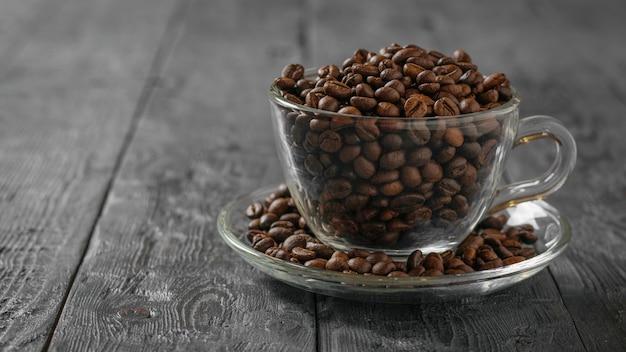 Tazza di caffè di vetro con chicchi di caffè e cucchiaio di metallo su un tavolo di legno nero. cereali per la preparazione della bevanda popolare.