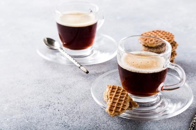 Tazza di caffè di vetro con i biscotti di syrupwaffles