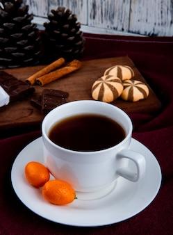 Tazza di caffè di vista frontale con kumquat e biscotti con cioccolato
