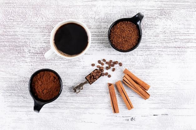 Tazza di caffè di vista superiore con caffè istantaneo e cannella sulla tavola bianca