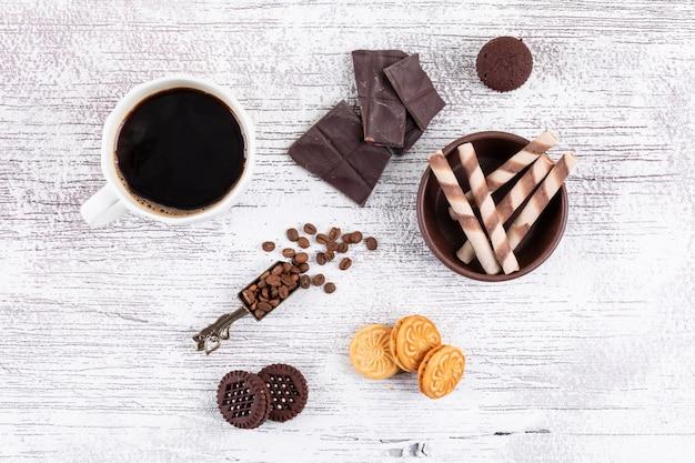Tazza di caffè di vista superiore con i biscotti e cioccolato sulla tavola bianca