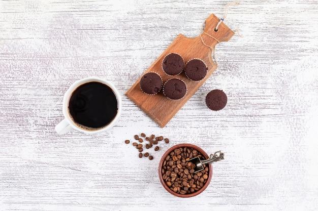 Tazza di caffè di vista superiore con i chicchi di caffè e i muffin del cioccolato sulla tavola bianca