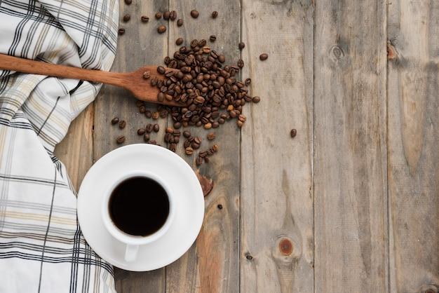 Tazza di caffè di vista superiore su fondo di legno