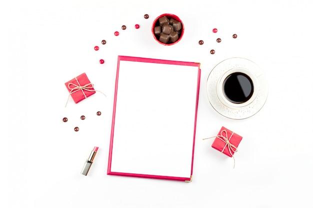 Tazza di caffè, dolci al cioccolato, confezione regalo e pezzo di carta bianco disteso. sfondo femminile.