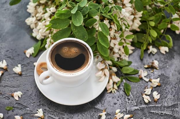 Tazza di caffè e acacia closeup. nutrizione. sfondo con una tazza di caffè e fiori di acacia.