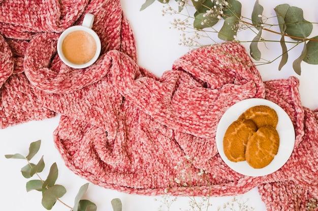 Tazza di caffè e biscotti sulla sciarpa decorata con foglie e fiori su sfondo bianco