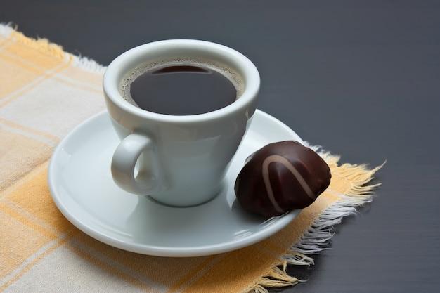 Tazza di caffè e caramelle al cioccolato sul tavolo