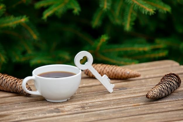 Tazza di caffè e chiave sulla tavola di legno con i rami attillati su fondo