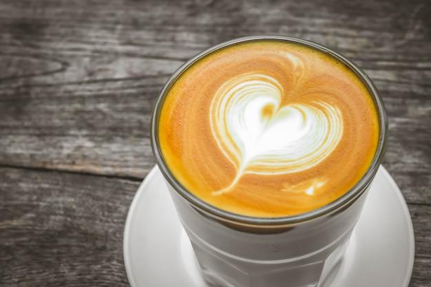 Tazza di caffè e chicchi di caffè del cuore su superficie di legno. vista dall'alto.