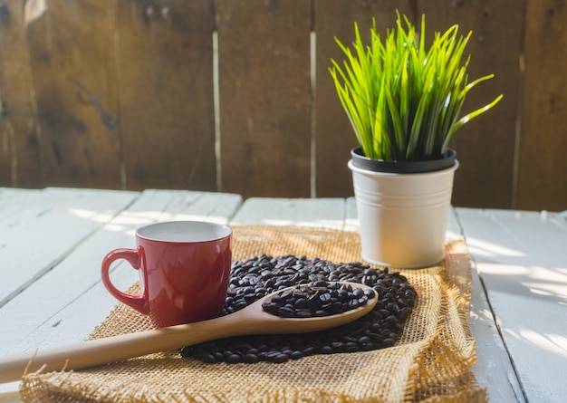 Tazza di caffè e chicchi di caffè rossi sulla tavola bianca di legno.