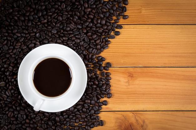 Tazza di caffè e chicchi di caffè su fondo di legno, vista superiore.