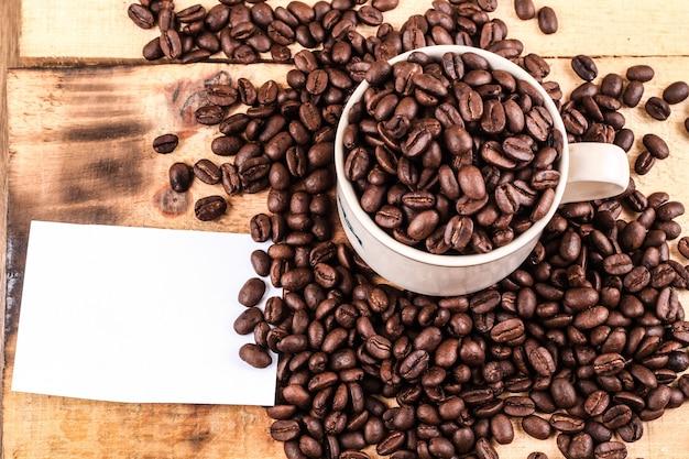 Tazza di caffè e chicchi di caffè su fondo in legno. vista dall'alto copia spazio