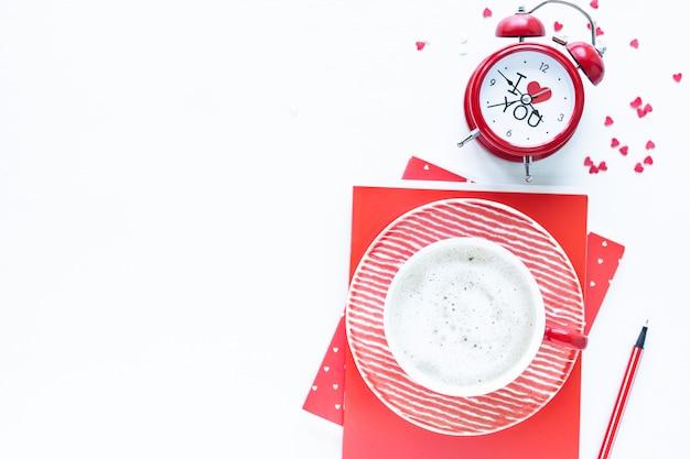 Tazza di caffè e contenitore di regalo rossi sulla tavola bianca. vista dall'alto con spazio di copia