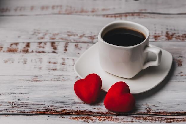 Tazza di caffè e coppia di cuori rossi
