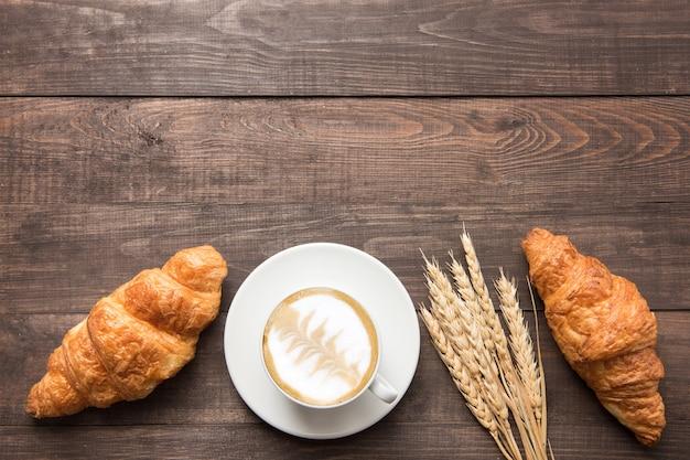 Tazza di caffè e cornetti freschi al forno su fondo di legno. vista dall'alto