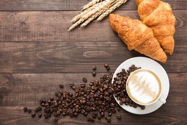 Tazza di caffè e croissant al forno freschi sulla tavola di legno. vista dall'alto