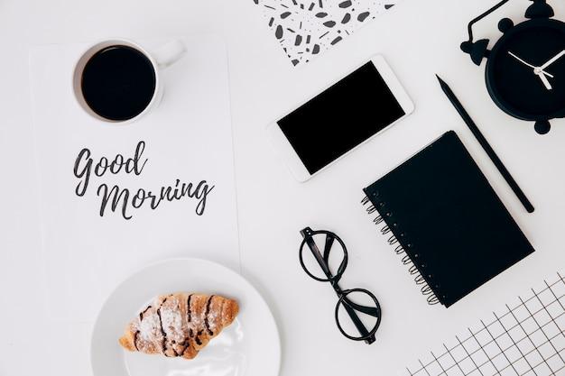 Tazza di caffè e croissant con messaggio di buongiorno su carta e ufficio stazionari sulla scrivania bianca