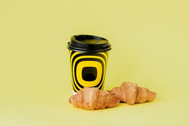 Tazza di caffè e croissant di carta su giallo