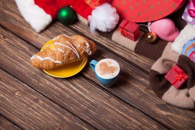 Tazza di caffè e croissant sulla priorità bassa di natale.