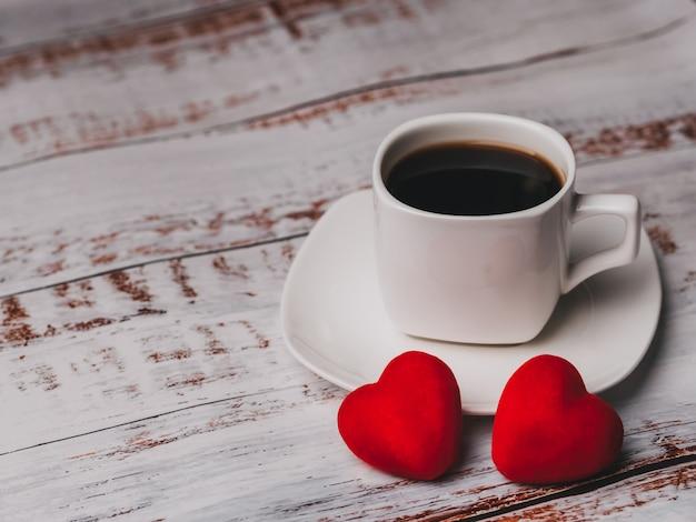 Tazza di caffè e cuori sulla tavola di legno, concetto della prima colazione di mattina il giorno di s. valentino