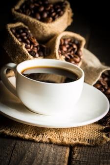 Tazza di caffè e fagioli. caffè espresso e un pezzo di torta con un ricciolo. tazza di caffè e chicchi di caffè sulla tavola.