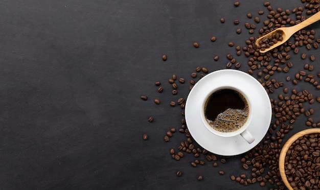 Tazza di caffè e fagioli sulla tavola nera