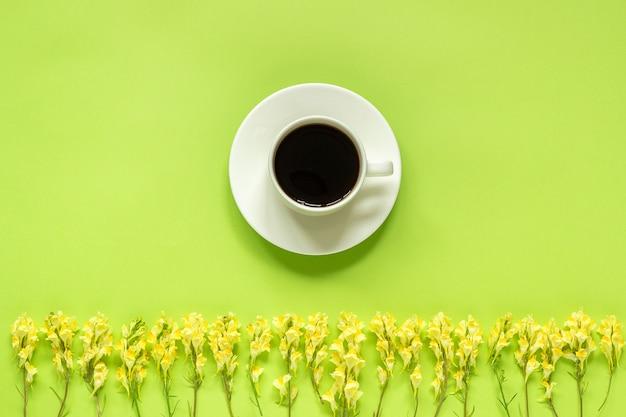 Tazza di caffè e fila giallo wild flowerson sfondo verde concetto buongiorno o ciao primavera