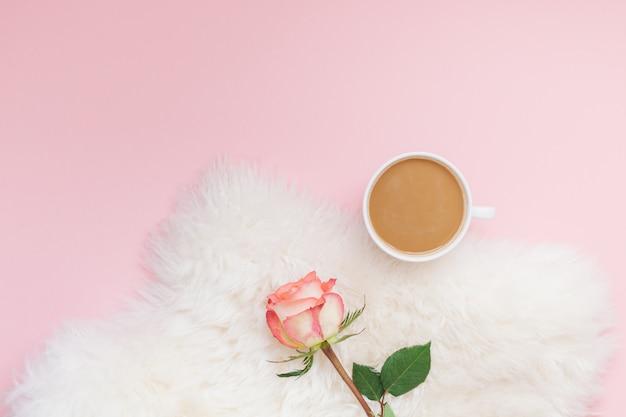 Tazza di caffè e fiore rosa sul rosa
