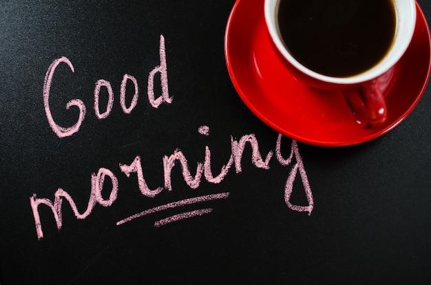 Tazza di caffè e il buongiorno dell'iscrizione.