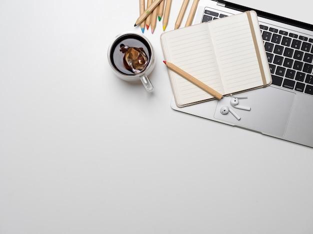 Tazza di caffè e laptop su un tavolo bianco