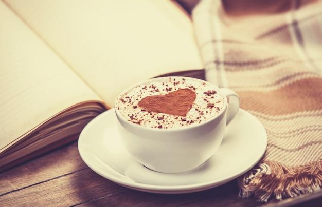 Tazza di caffè e libro con sciarpa