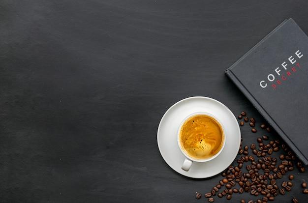 Tazza di caffè e libro sul fondo del pavimento in legno nero. vista dall'alto. spazio per il testo