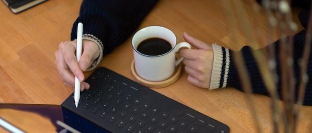Tazza di caffè e mano destra femminili della tenuta della mano sinistra facendo uso della compressa digitale sopra il worktable