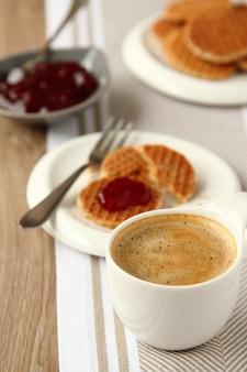 Tazza di caffè e mini stroopwafels sciroppi con marmellata