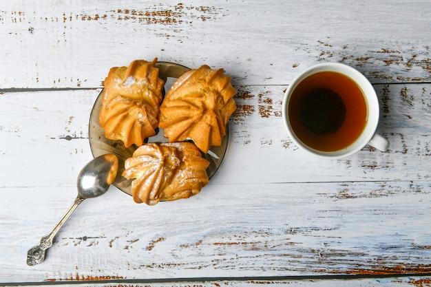 Tazza di caffè e pasta cremosa. composizione della tazza di caffè e della pasticceria. tazza di caffè e pasticceria dolce con crema ripieno su una luce