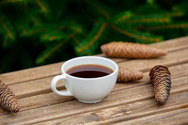 Tazza di caffè e pigne sulla tavola di legno con i rami attillati su fondo