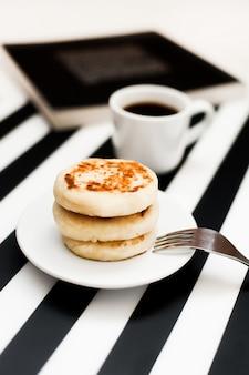 Tazza di caffè e prodotti da forno su sfondo bianco e nero a strisce.