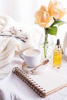 Tazza di caffè e rose bianche con il taccuino sul letto e sul plaid bianchi, luce accogliente di mattina.