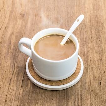 Tazza di caffè e sottobicchiere della bevanda su fondo di legno.